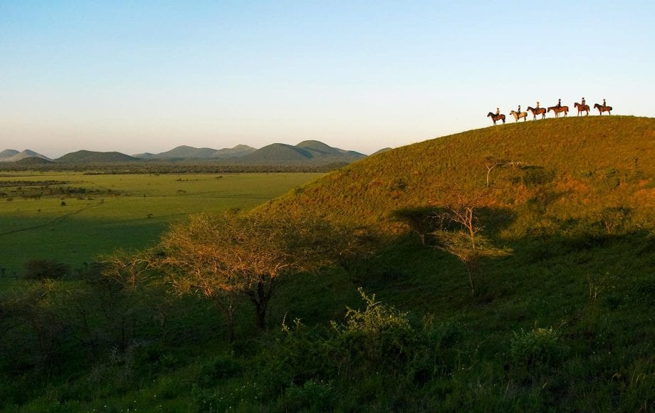 Horseback riding in the wild on a hill at Chyulu Hills