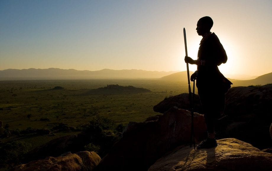Man standing against setting sun on top of Chyulu Hills
