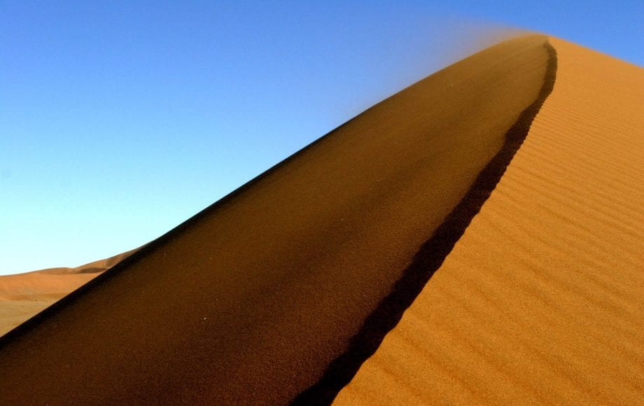 Sand blowing away with the wind at Sossusvlei Namib Desert