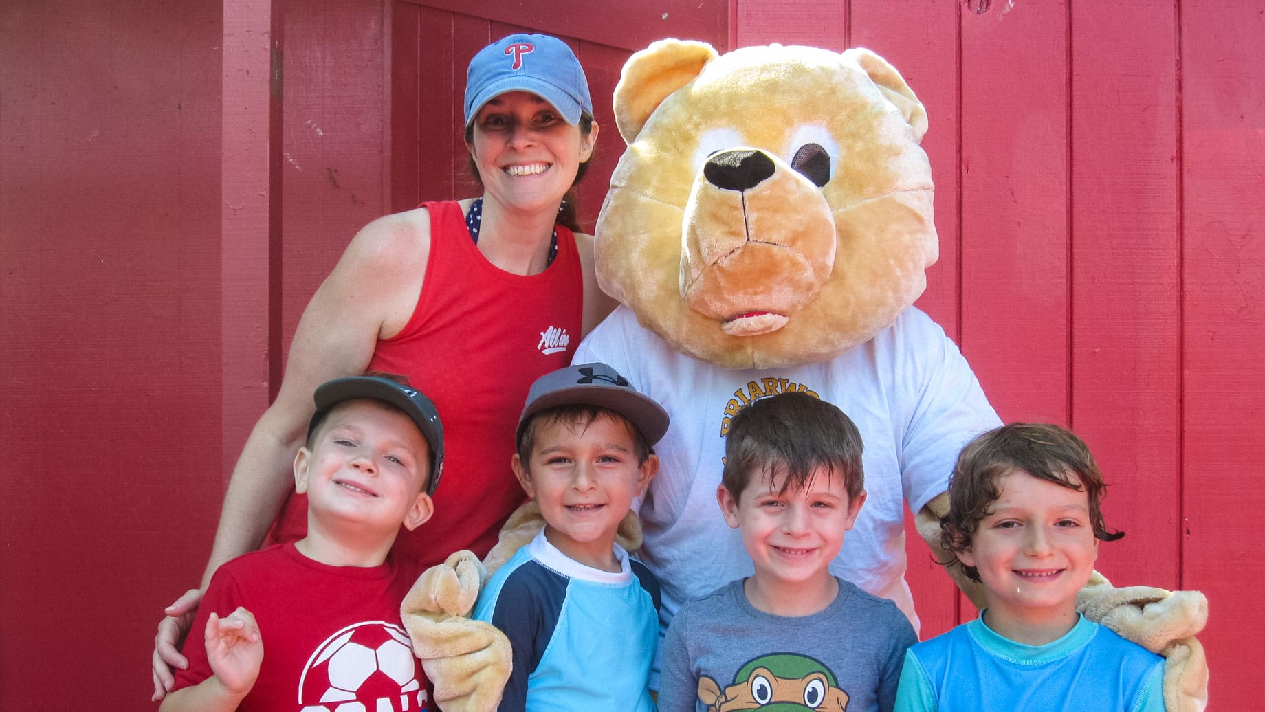 Staff, mascot, and campers smiling